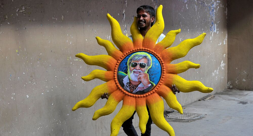A man carries a plaster of Paris artwork featuring actor Rajinikanth outside a movie theatre on the eve of the release of Tamil film Kabali in Bengaluru, India, 21 July 2016