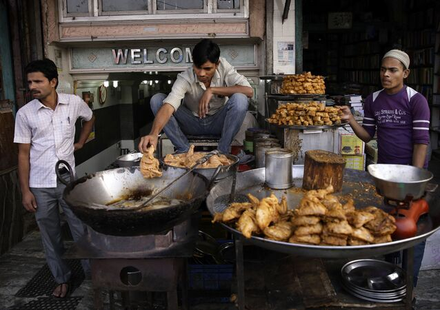 In this Tuesday, Nov. 12, 2013 photo, a cook uses his hand to release pieces of chicken into hot oil at a street side food joint in New Delhi, India
