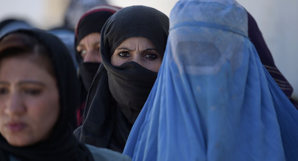 Afghan women line up to receive food donations during the month of Ramadan in Kabul on June 23, 2016