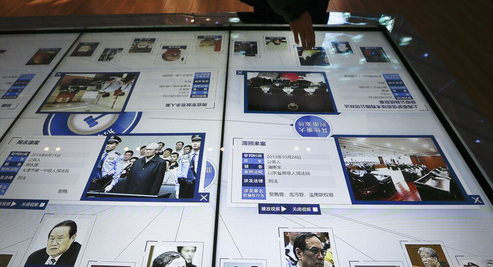A visitor, top, looks at an electronic screen displaying images and convicted corruption charges of China's fallen politicians, Bo Xilai, bottom second right, Zhou Yongkang, bottom left, and other senior officials, at the China Court Museum in Beijing, Tuesday, Jan. 12, 2016