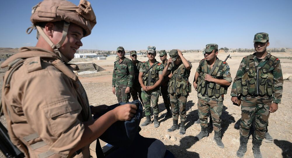 A Russian serviceman, left, trains Syrian soldiers to search and detect explosive devices in Palmyra. File photo