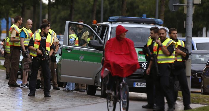 Man In Red Poncho Sits Near Police During Munich Shooting