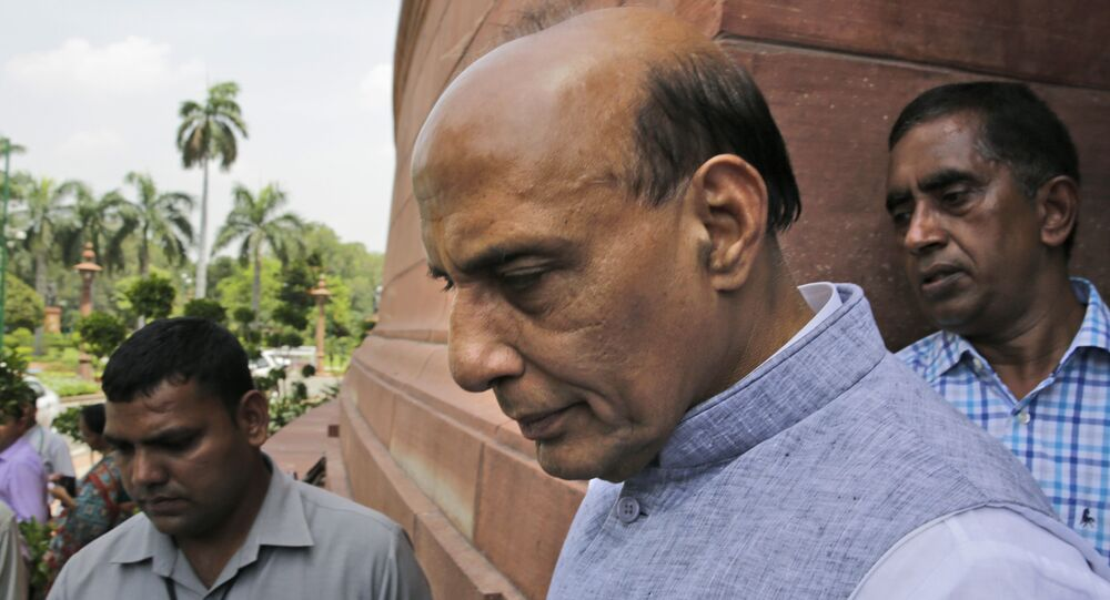 Indian Home Minister Rajnath Singh, centre, comes out from parliament house.