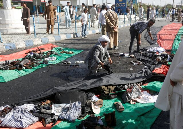 Afghan men remove the clothes of victims after a suicide attack in Kabul, Afghanistan July 23, 2016.