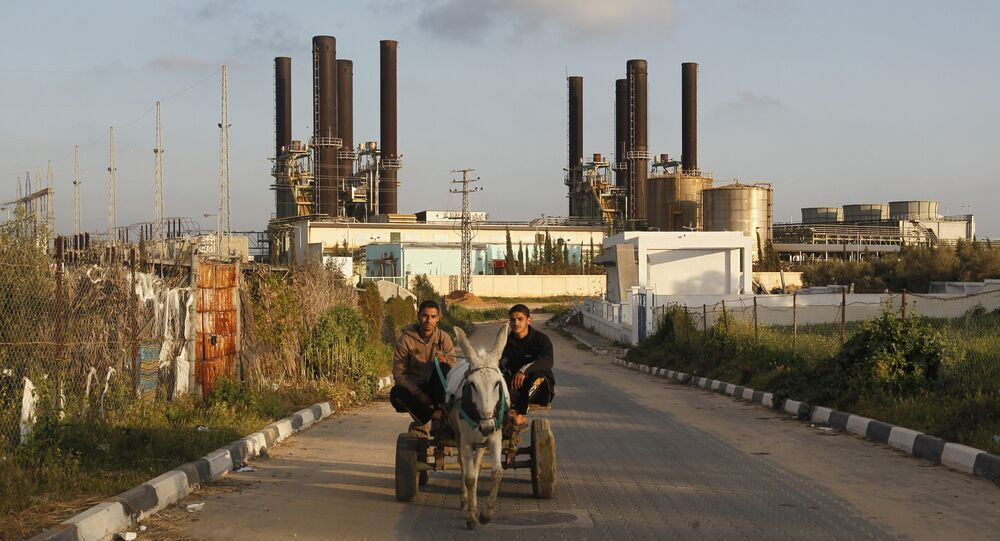 Palestinians ride a donkey-pulled cart past Gaza's sole power plant in Nusairat