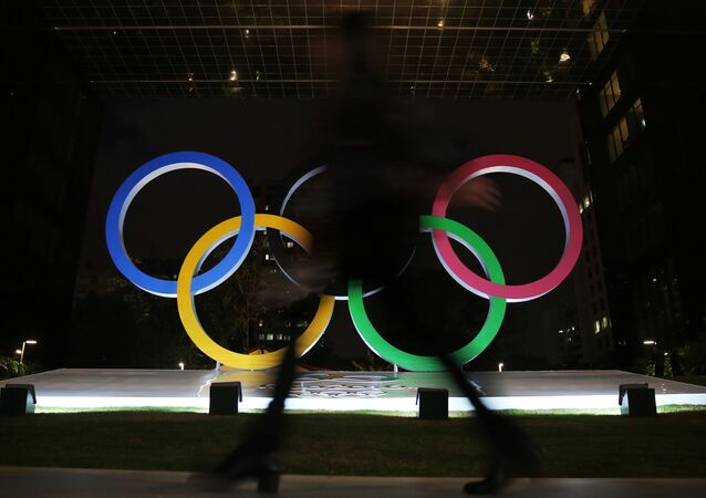 A woman walks past Olympic rings placed at the entrance of a office building ahead of the Rio 2016 Olympic Games, in Sao Paulo, Brazil, July 19, 2016.