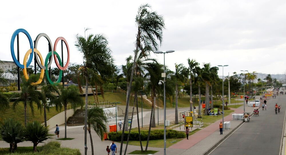 People walk near Olympic rings placed at Madureira Park ahead of the Rio 2016 Olympic Games in Rio de Janeiro, Brazil, July 17, 2016.