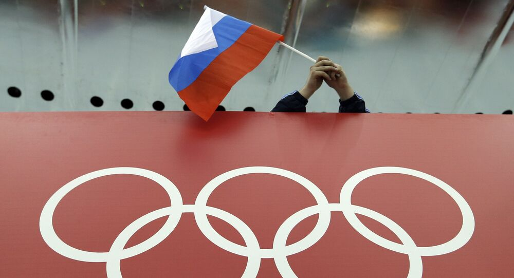 Russian skating fan holds the country's national flag over the Olympic rings before the start of the men's 10,000-meter speedskating race at Adler Arena Skating Center during the 2014 Winter Olympics in Sochi, Russia. (File)