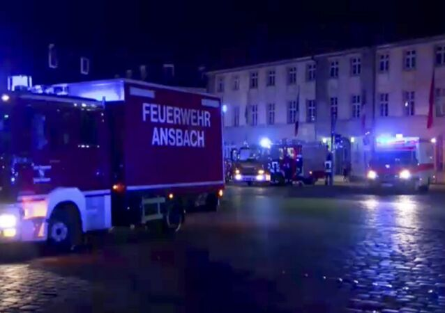 In this image taken from video fire trucks and ambulances stand in the city center of Ansbach near Nuremberg, southern Germany, Monday morning, July 25, 2016, after a man was killed when an explosive device he was believed to be carrying went off near an open-air music festival, injuring 12 others.