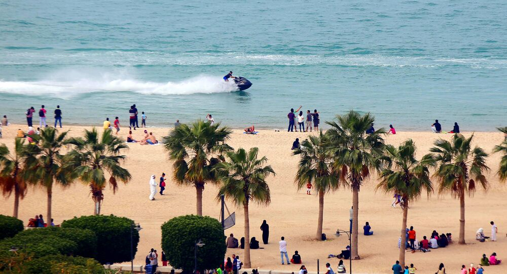A jet-skier drives past people on a beach in the Salmiya district of Kuwait City