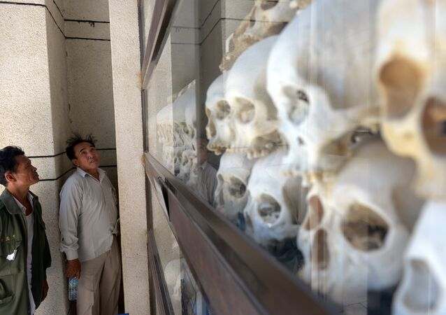 Cambodian men looks at skulls of victims killed by the Khmer Rouge regime at the Choeung Ek killing fields memorial