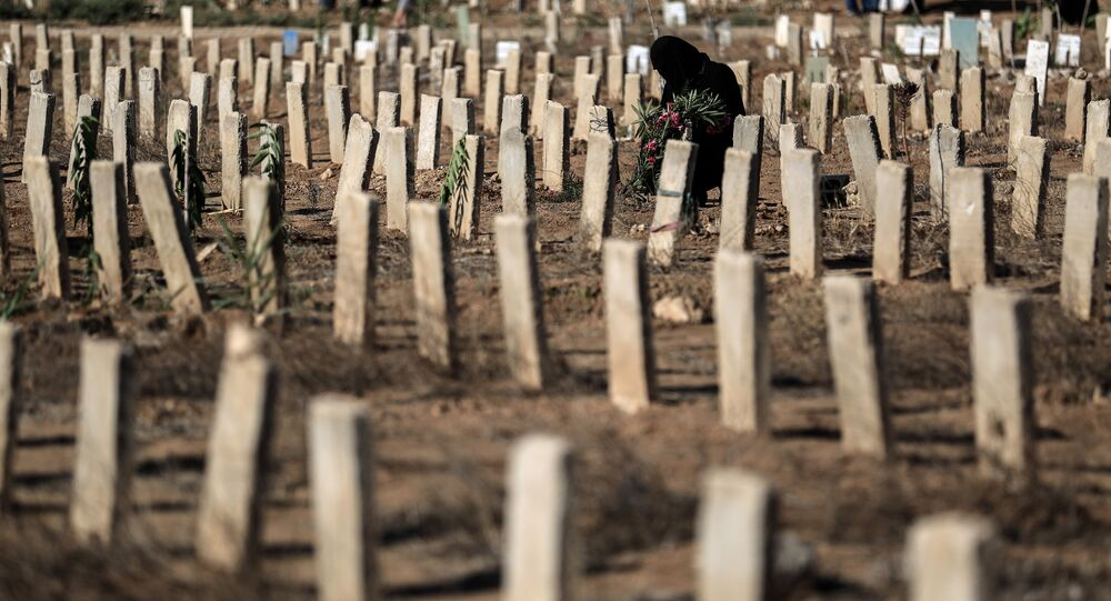 A woman visits the grave of a relative in the rebel-held town of Douma, east of the capital Damascus