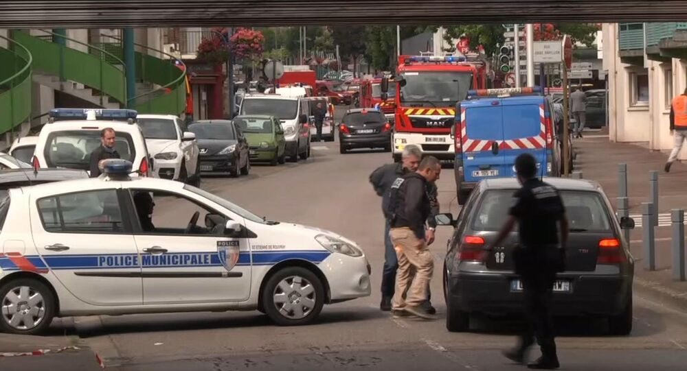 In this grab made from video, police officers speak to a driver as they close off a road during a hostage situation in Normandy, France, Tuesday, July 26, 2016.