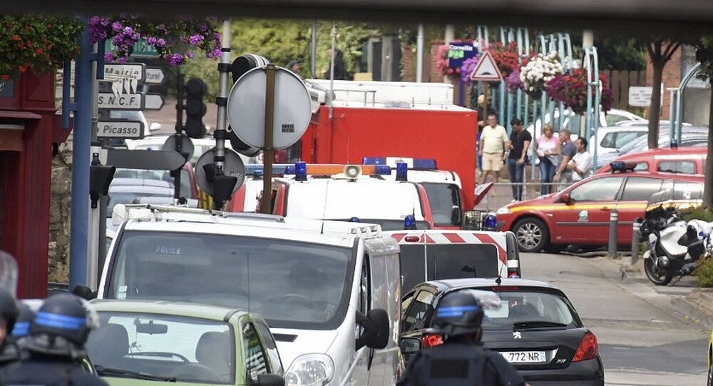 Police and rescue workers stand at the scene after two assailants had taken five people hostage in the church at Saint-Etienne-du -Rouvray near Rouen in Normandy, France