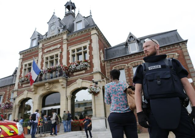 A French police officer stands guard by Saint-Etienne-du-Rouvray's city hall following a hostage-taking at a church in Saint-Etienne-du-Rouvray, northern France