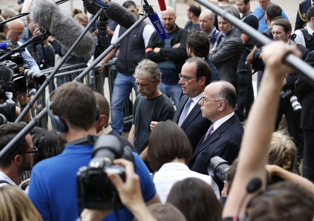 French President Francois Hollande (C) flanked by Hubert Wulfranc mayor of Saint-Etienne-du-Rouvray (L) and French Interior Minister Bernard Cazeneuve (R), speaks to the press as he leaves the Saint-Etienne-du-Rouvray's city hall following a hostage-taking at a church of the town on July 26, 2016 that left the priest dead.
