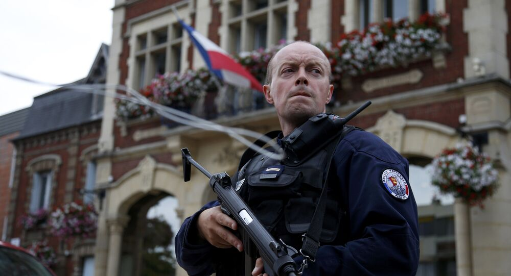 A policeman secures a position in front of the city hall after two assailants had taken five people hostage in the church at Saint-Etienne-du -Rouvray near Rouen in Normandy, France, July 26, 2016.