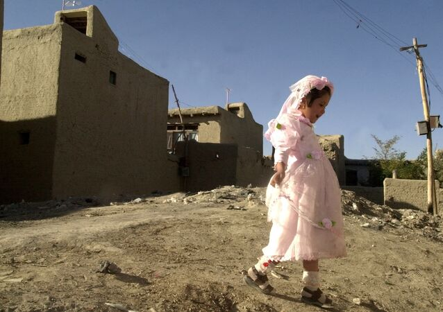 Girl plays outside during a wedding party in Kabul, Afghanistan