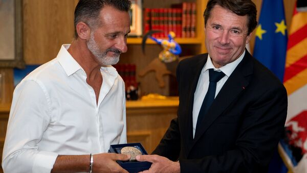 President of the Provence Alpes Cote d'Azur region and former Nice mayor Christian Estrosi (R) gives to Franck, one of the three 'heroes' of the July 14 attack in Nice, the city's medal at the City hall in Nice, southeastern France - Sputnik International