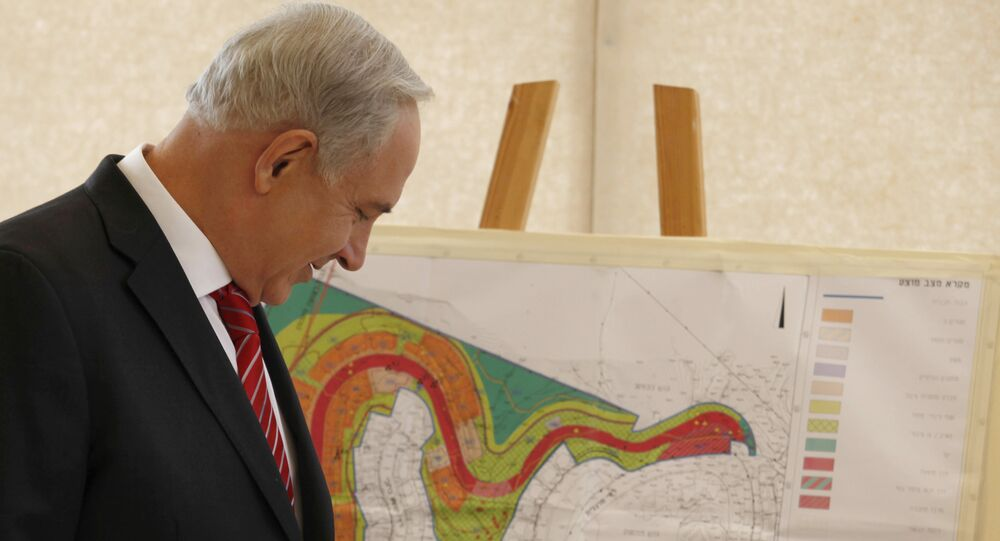 Israeli Prime Minister Benjamin Netanyahu looks at a map of the area where Israel plans to build some 800 new housing units during his visit to the east Jerusalem Jewish neighborhood of Gilo.