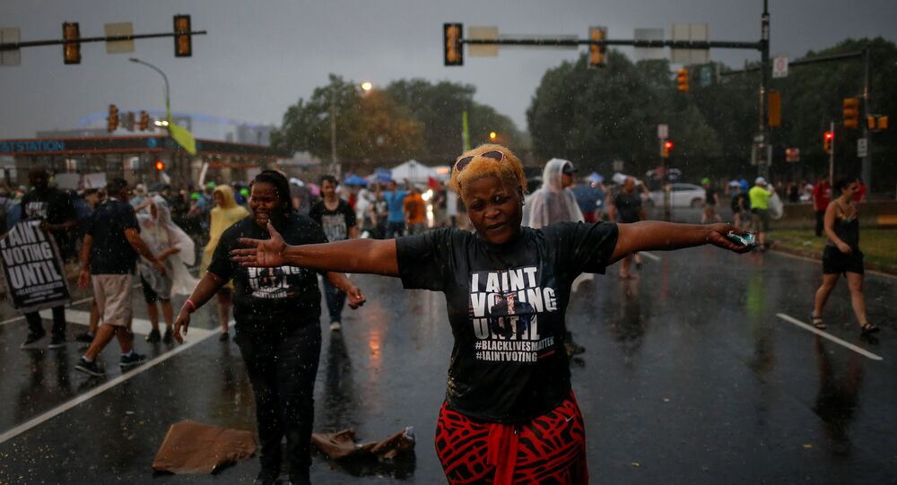 Black Lives Matter activists react to heavy rain fall as they gather to protest outside the site of the 2016 Democratic National Convention in Philadelphia, Pennsylvania July 25, 2016.