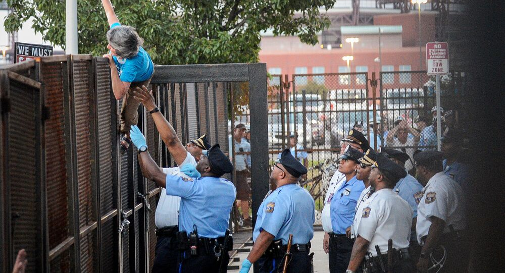 A protester is detained by police after climbing over a barrier near the site of the Democratic National Convention in Philadelphia, Pennsylvania, U.S., July 26, 2016