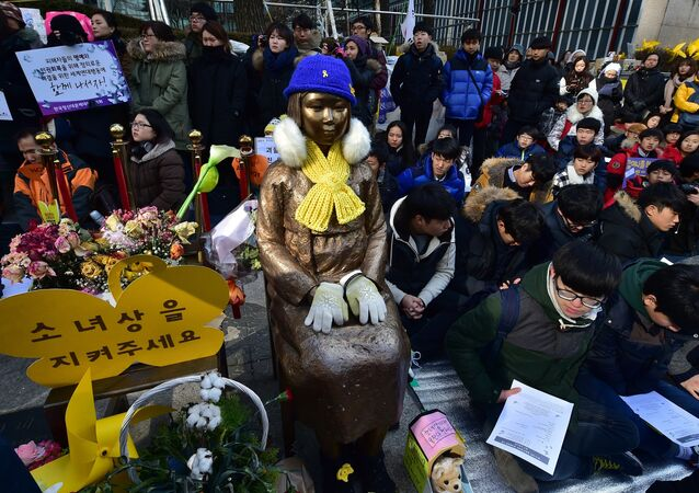 South Korean students sit near a statue (C) of a teenage girl symbolizing former comfort women who served as sex slaves for Japanese soldiers during World War II, during a weekly anti-Japanese demonstration in front of the Japanese embassy in Seoul (File)