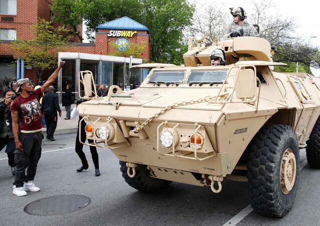 Police armoured cars drive down a Baltimore street as people begin to celebrate in Baltimore, Maryland May 1, 2015 following the decision to charge six Baltimore police officers -- including one with murder -- in the death of Freddie Gray