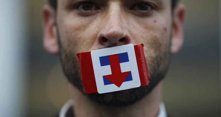 A former Bernie Sanders delegate wears a Hillary Clinton presidential campaign sticker over his mouth as he protests during the third session at the Democratic National Convention in Philadelphia, Pennsylvania, U.S. July 27, 2016.