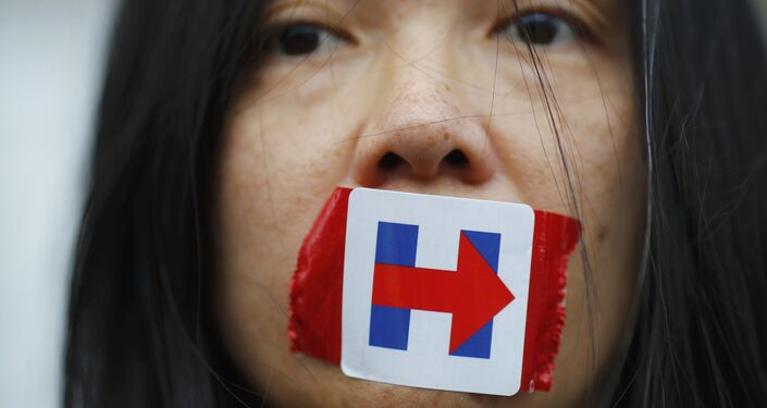 A former Bernie Sanders delegate wears a Hillary Clinton presidential campaign sticker over her mouth as she protests during the third session at the Democratic National Convention in Philadelphia, Pennsylvania, U.S. July 27, 2016.