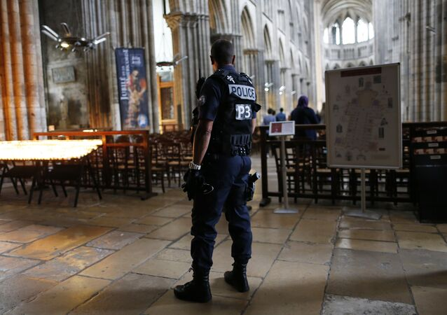 A policeman stands guard while people arrive for a Mass at the Rouen Cathedral, on July 27, 2016 in Rouen, to pay tribute to the priest Jacques Hamel, killed on July 26 in a church of Saint-Etienne-du-Rouvray during a hostage-taking claimed by Islamic State group