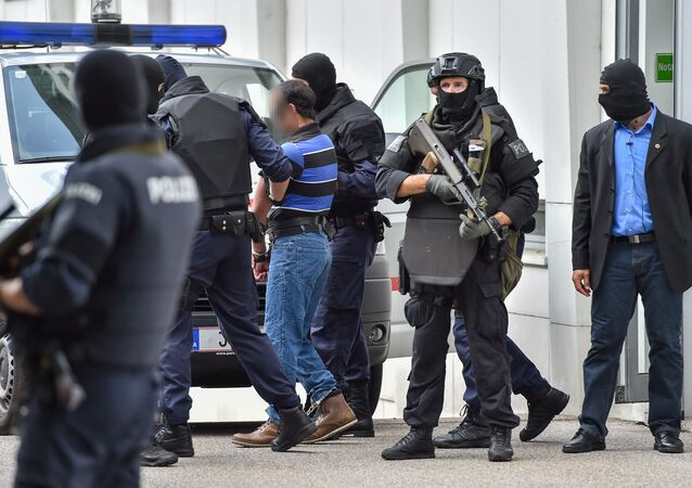 A suspected member of the Islamic State jihadist group is led away by Austrian police from the court in Linz, Austria, on July 27, 2016