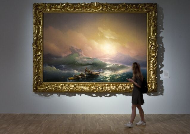 A visitor is seen near the painting The Ninth Wave displayed at the Ivan Aivazovsky. 200th Birthday exhibition at the Tretyakov Gallery on Krymsky Val in Moscow