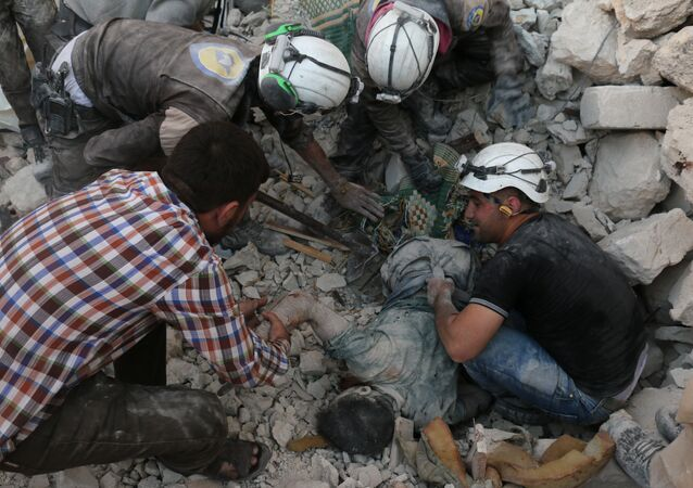 Syrian civil defence volunteers remove the body of a man from the rubble of destroyed buildings following reported airstrikes on April 27, 2016 in the rebel-held eastern neighbourhood of Bab al-Nayrab in the city of Aleppo