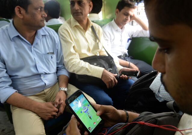 In this photograph taken on July 28, 2016 an Indian officegoer plays the Pokemon Go game on his phone while commuting in a local train in Mumbai