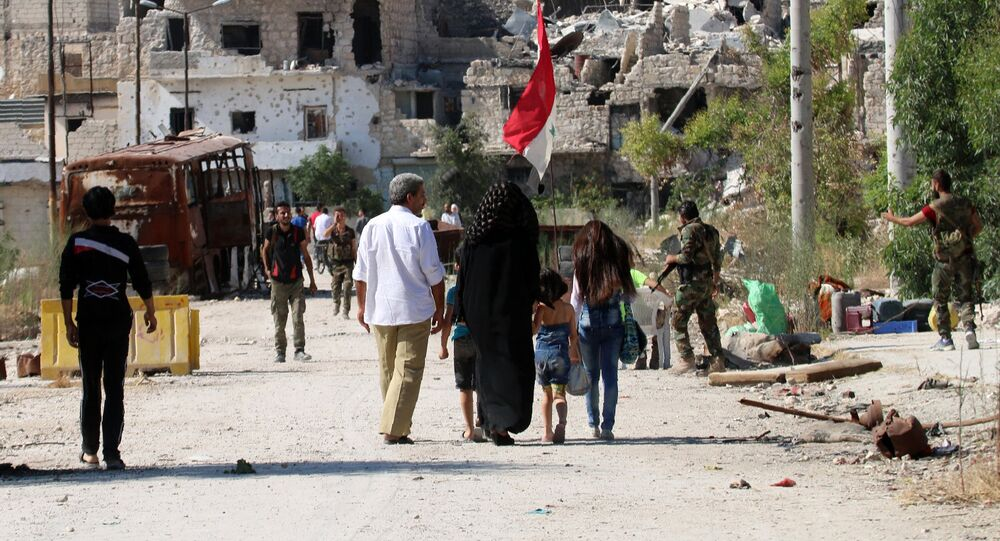 Syrian government forces secure a street as civilians come back to the neighbourhood of Bani Zeid, on Aleppo's northern outskirts on July 29, 2016