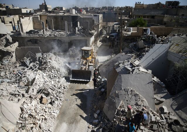 A front loader remove debris from a site hit by an airstrike in the rebel held Douma neighborhood of Damascus (File)