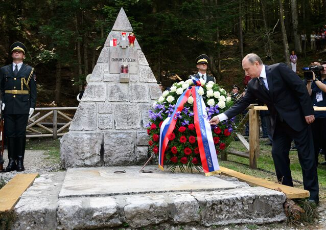 Russian President Vladimir Putin (R) lays a wreath during a ceremony at a Russian Chapel at the Vrsic mountain pass in northern Slovenia