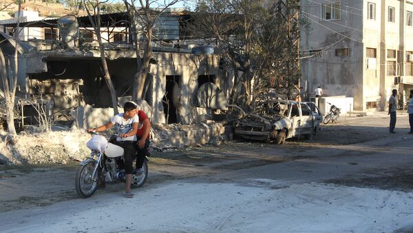People inspect the damage as they stand near a Save the Children sponsored maternity hospital after an airstrike in the rebel-controlled town of Kafer Takhareem in Idlib province, Syria - Sputnik International