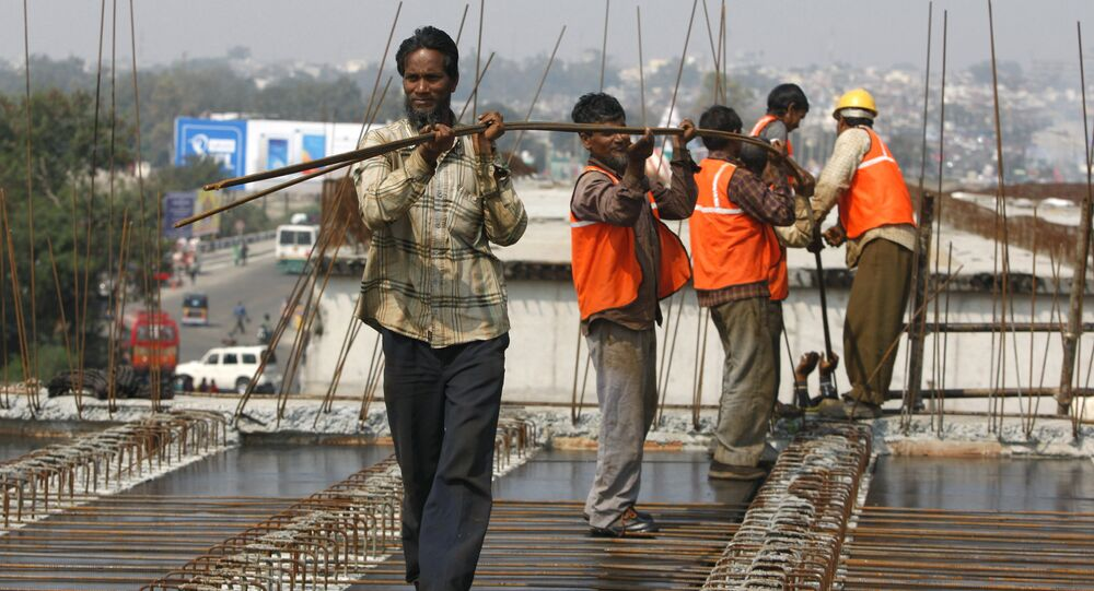 Indian workers carry metal rods on an overpass bridge in Jammu, India