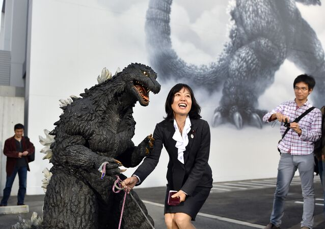 Japan's star monster Godzilla (front L) celebrates with a fan after an awards ceremony at Toho Studio in Tokyo's Setagaya Ward on November 3, 2014.
