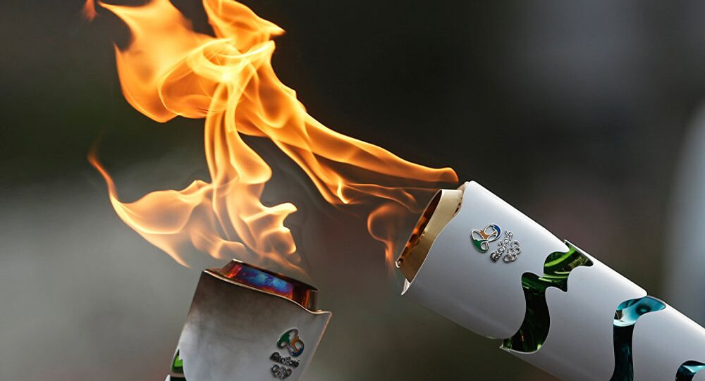 Brazilian residents pass the Olympic torch at Independence Park upon the flame's arrival in Sao Paulo, Brazil, on July 24, 2016