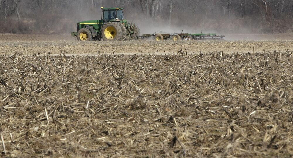 In this photo taken Thursday, Jan. 30, 2014, a farmer takes advantage of dry weather to till a field in preparation for spring planting near England, Ark.