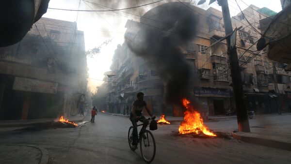 A man rides a bicycle past burning tyres, which activists said are used to create smoke cover from warplanes, in Aleppo, Syria August 1, 2016 - Sputnik International