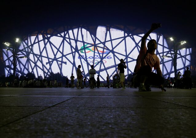 People walk past the Bird's Nest National Stadium as it is illuminated with the logo of the 2016 Rio Olympic Games in Beijing, China, 4 August 2016