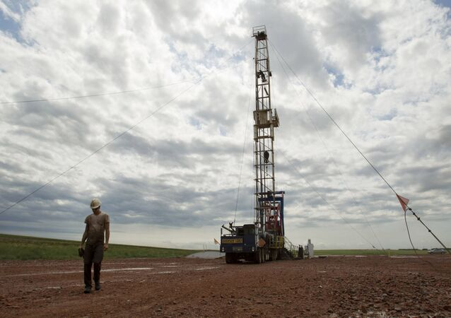 In this Tuesday, July 26, 2011 file photo, Austin Mitchell walks away from an oil derrick outside of Williston, N.D.