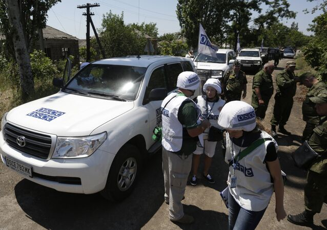 Members of the Organization for Security and Co-operation in Europe (OSCE) stand in the village of Shyrokyne, Donetsk region on July 4, 2015