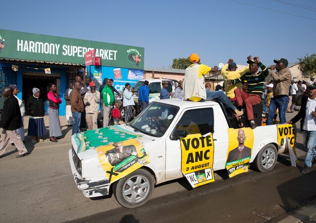An ANC party vehicle appeals for votes as locals are seen outside a voting station during the Local Government elections in Diepsloot township, north of Johannesburg, South Africa