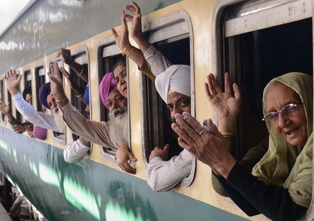 Indian Sikh pilgrims pose for a photograph as they wave from a train bound for Pakistan at a railway station in Amritsar on November 15, 2013
