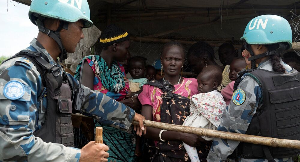 United Nations peacekeepers control South Sudanese women and children before the distribution of emergency food supplies at the United Nations protection of civilians (POC) site 3 hosting about 30,000 people displaced during the recent fighting in Juba, South Sudan, July 25, 2016